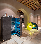 Open bar cabinet and modern light sculpture in rustic country house