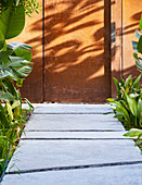 Concrete path in tropical garden leading to weathering steel wall