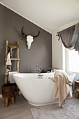 Free-standing bathtub and rustic decorations in bathroom in natural shades