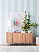 Sideboard with table lamp, glass decoration and flower sprig against striped wall