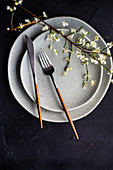 Tischgedeck mit grauen Tellern und blühendem Pfirsichzweig
