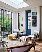 White armchairs with footstools below skylight next to terrace doors
