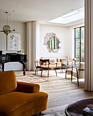 Grand piano and yellow velvet chair in open-plan living area