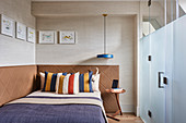 Striped pillows on double bed against walls upholstered in leather