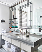 Metal frame and shelves on mirrored wall above washstand