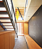 Custom wooden bench and chalkboard wall in stairwell
