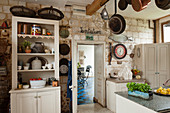Dresser in rustic country-house kitchen with stone wall