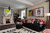 Ziffernblatt-Teppich vor schwarzem Sofa mit farbenfrohen Designer-Kissen