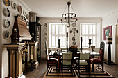 Designer chairs and mantelpiece decorated with pillars and decorative wall plates in stylish dining room