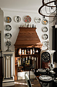 Hölzerner Kamin eklektisch dekoriert mit Säulen sowie Vasen- und Tellersammlung