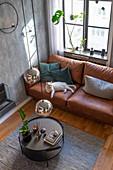 Weiße Katze auf braunem Ledersofa im Wohnzimmer in gedeckten Farben