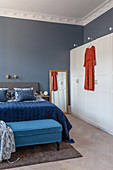 Blue velvet throw on bed and bedroom bench next to white modern wardrobe