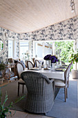 Wicker chair and upholstered chairs in dining room with floral wallpaper