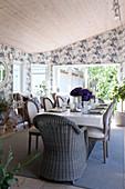 Korbstuhl und Polsterstühle im Esszimmer mit floraler Tapete