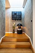 Table lamp on pouffe and floor case below wall-mounted cabinet on landing