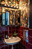 Sink in guest toilet with dark-red wall tiles and floral wallpaper