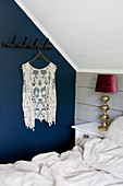 Lace waistcoat hanging from row of pegs on blue bedroom wall