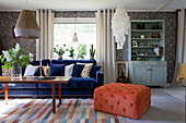 Dark blue sofa and orange pouffe in vintage-style living room