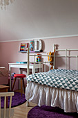Metal bed with valance in child's bedroom with pink wall