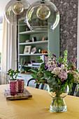 Vase of summer flowers in vintage-style dining room