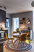 Yellow shell chairs around dining table on round rug in modern kitchen