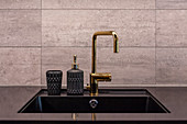 Golden tap fitting and soap dispenser with structured surface on sink