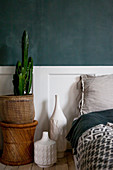 Cactus in basket and vases next to bed in bedroom
