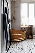 Free-standing wooden bathtub on stone floor of bathroom