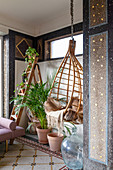 Old mosaic floor and bamboo hanging chair with fur blanket in conservatory