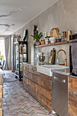 Stylish kitchen with wooden units and brick floor