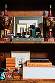 Collection of pictures, books and ornaments on wooden shelves