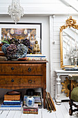 Antique chest of drawers next to gilt mirror on console table