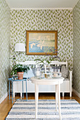 Bench, houseplant, lamp and painting on floral wallpaper in niche