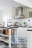Open-sided island counter and chequered floor in L-shaped kitchen