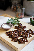 Chocolate shards with salt and rosemary on wooden board