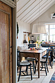 Black spoke-back chairs around wooden table in rustic kitchen-dining room