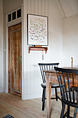 Black spoke-back chairs at rustic table in wooden house