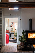 Roaring fire in wood-burning stove and view into bedroom