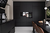 Brown leather chairs at dining table in kitchen with black cabinets