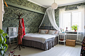 Bed with valance and canopy in bedroom with vintage-style wallpaper