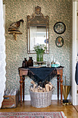 Old mirror and console table in hallway with vintage-style wallpaper
