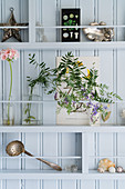 Flowers and vintage-style ornament on shelves on pale blue board wall