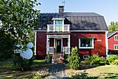 Rotes Schwedenhaus mit sommerlichem Vorgarten