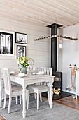 Dining table against board wall and wood-burning stove with row of pegs around stove pipe