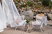 Sitzplatz mit Holzblock als Tisch und wehenden Gardinen am Strand
