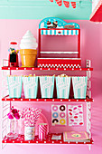 Bags of popcorn, ice-cream-shaped lamp, bubblegum machine and party utensils on red-and-white polka-dot shelves