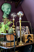 Gilt lamps on lavishly decorated, vintage-style serving trolley