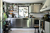 Stainless steel cabinets and traditional, wood-fired stove in large kitchen