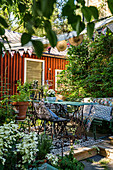 Vintage garden furniture on wooden terrace in idyllic summery garden