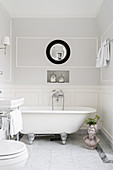 Free-standing bathtub in bathroom with panelled wainscoting